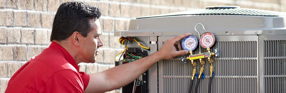 HVAC repair man checking gauge on air conditioner